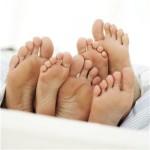 Zes blote voeten in bed